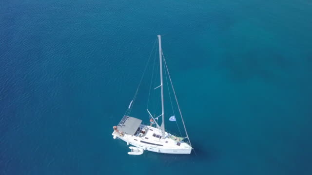 anchored sailboat in a bay, aerial drone view near islands in greece. - anchored stock videos & royalty-free footage