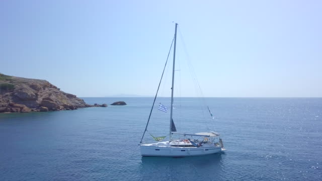 anchored sailboat in a bay, aerial drone view near islands in greece. - anchored stock-videos und b-roll-filmmaterial