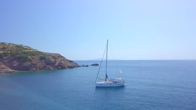 anchored sailboat in a bay, aerial drone view near islands in greece. - mediterranean culture stock videos & royalty-free footage