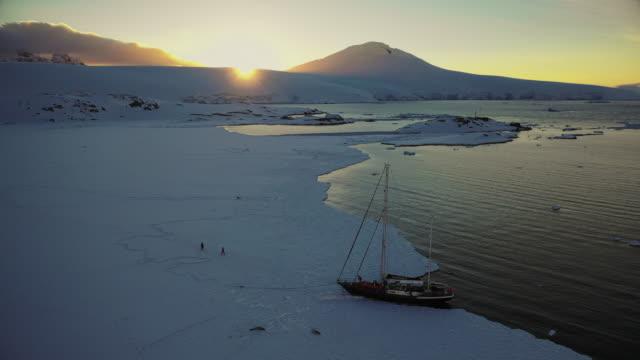 vídeos de stock e filmes b-roll de anchoring the sail boat to the sea ice near port lockroy - explorador