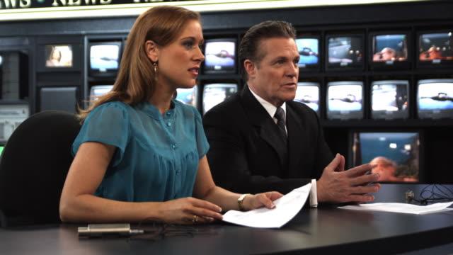 MS Anchors talking at newsroom desk, Dallas, Texas, USA