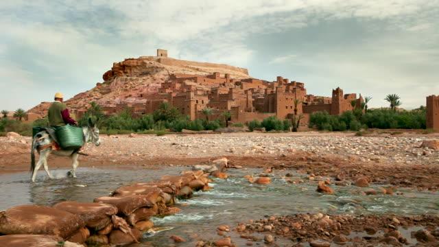 vídeos y material grabado en eventos de stock de ancient fortress. man and donkey crossing tirza river, ait-ben-haddou, morocco - burro