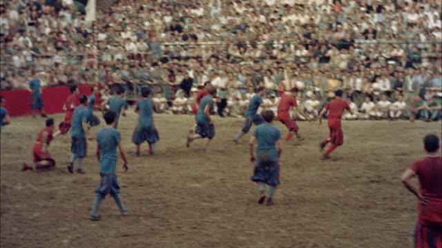ws pov ancient game of football being played between blue and red teams / florence, italy - 1954 bildbanksvideor och videomaterial från bakom kulisserna
