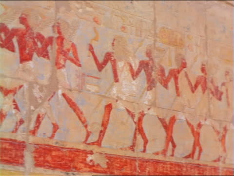 pan ancient hieroglyphics + carvings on wall of ruins / mortuary temple of queen hatshepsut / egypt - painting stock videos & royalty-free footage