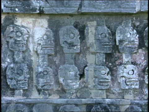 ancient mayan carvings of skulls decorate a stone wall. - mayan stock videos & royalty-free footage