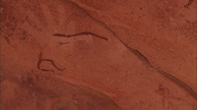 ancient petroglyphs decorate a rock formation wall. - archaeology stock videos & royalty-free footage