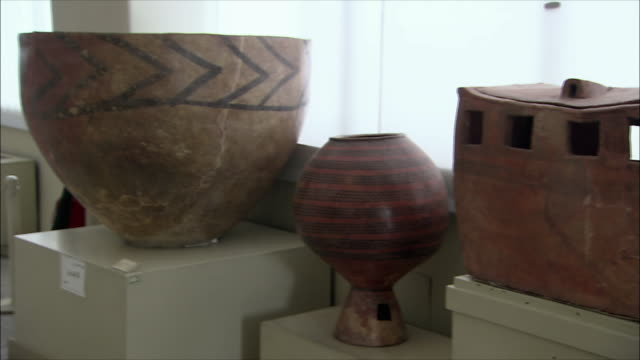 vídeos de stock e filmes b-roll de cu pan ancient pottery vessels in national museum of iran, tehran, iran - quatro objetos