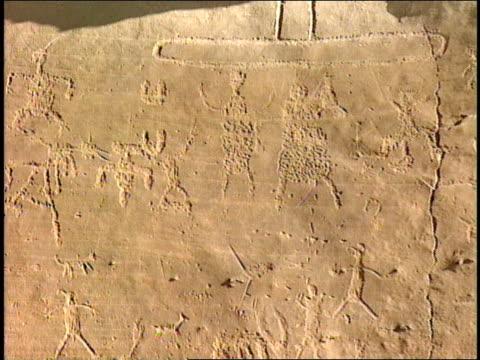 ancient pueblo petroglyphs cover a stone wall. - pueblo bonito stock videos & royalty-free footage