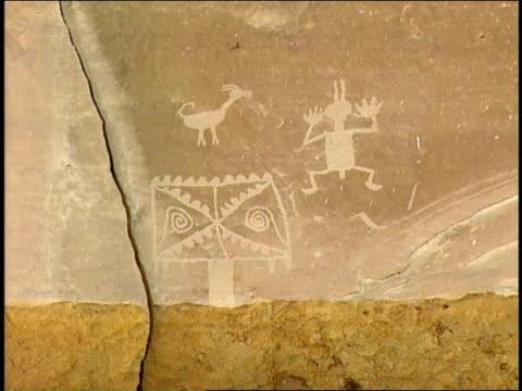 ancient pueblo petroglyphs depict an animal, a person and a symbol. - pueblo bonito stock videos & royalty-free footage