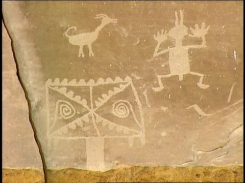 ancient pueblo petroglyphs depict an animal, a person and a symbol. - prehistoric art stock videos & royalty-free footage