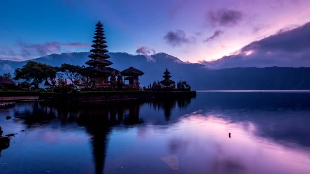 ancient pura ulun danu bratan temple reflection with colorful sky at sunrise. bali, indonesia - pura ulu danau temple stock videos & royalty-free footage