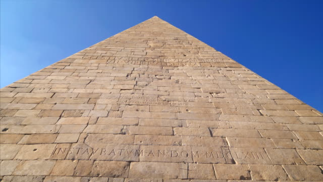 ancient roman pyramid of cestius against blue sky in rome, italy - pyramid stock videos and b-roll footage