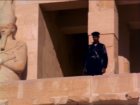 pan ancient statue + soldier guarding temple ruins / mortuary temple of queen hatshepsut / egypt - tempio di hatshepsut video stock e b–roll