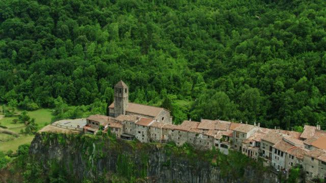 antica città in pietra sulla scogliera circondata da una lussureggiante foresta verde, castellfollit de la roca - colpo di drone - roca video stock e b–roll