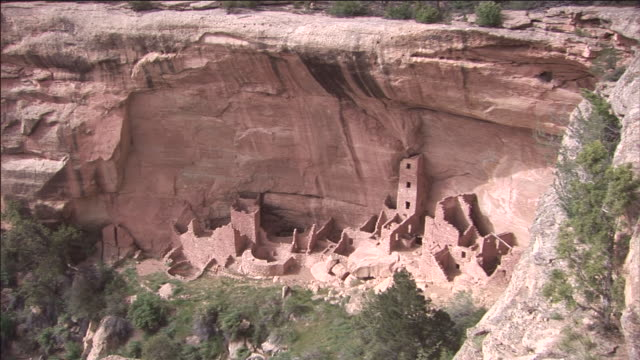 ancient stone dwellings stand at the base of a cliff in colorado. - mesa verde nationalpark stock-videos und b-roll-filmmaterial