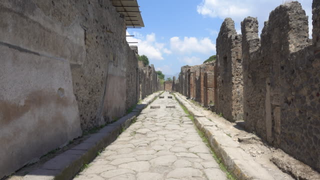 ancient stone road street in the ancient ruins historic landmark of pompeii, italy, europe. - old ruin stock videos & royalty-free footage