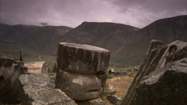 ancient stone structures lie on a hillside at the delphi archeological site. - ancient greece stock videos & royalty-free footage