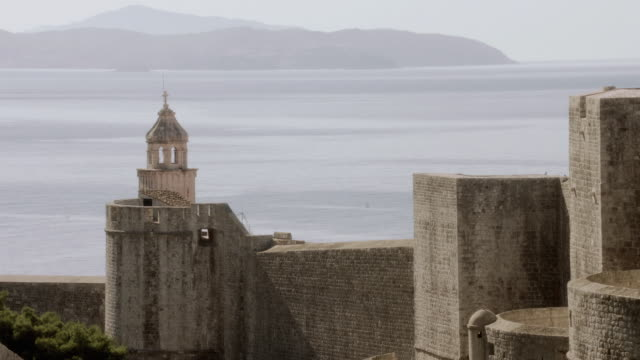 ha ancient walls overlooking the sea under hazy skies - formato panoramico con bande nere video stock e b–roll