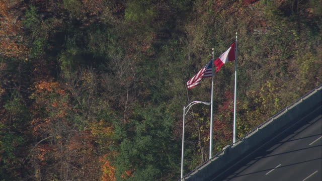 vídeos de stock, filmes e b-roll de aerial u.s. and canadian flags waving in the wind at the border crossing with autumn foliage beyond / new york, united states - canadá