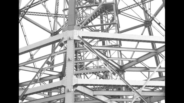 vidéos et rushes de and circular pan inside mooring mast of steel girders / mooring mast, monoplanes in foreground / man climbs mooring mast and then sits, monoplanes... - montréal