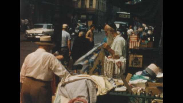 and cus of an old jewish man wearing a kippah or yamaka folding a piece of cloth in front of his general wares shop in new york's lower east side.... - new york city 1950s stock videos & royalty-free footage