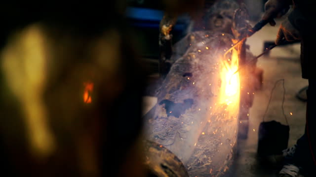 SLO MO and Dolly Shot Welder welding steel sculpture and repair detail of the Buddha while sparks and smoke.