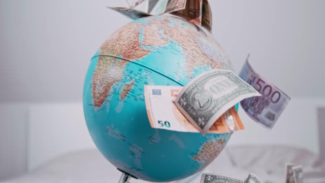 US and Euro currency falling over spinning globe, super slow motion
