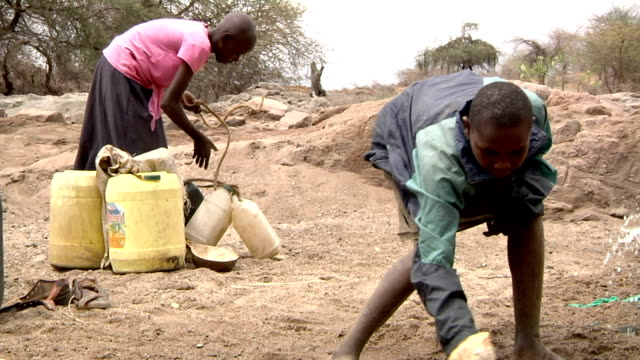and girl picking up empty gallons behind him Boy spilling dirty water out of small water well on July 29 2011 in Road from Garissa to Dadaab Kenya