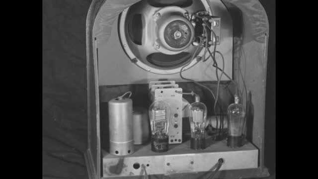 and hand installs radiotron vacuum tube in the back of a piece of electronic equipment, possibly a radio / note: exact month/day not known - rca stock videos & royalty-free footage