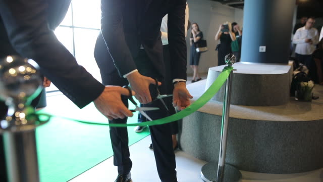 ceo and his assistant cutting a green ribbon at opening ceremony. they are starting a new business - ceremony stock videos & royalty-free footage