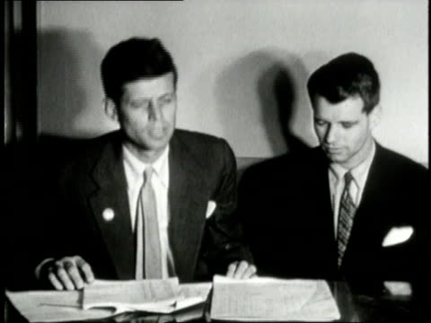 rfk and jfk standing together / rfk sitting at table with jfk reviewing election results / jfk covered in confetti surrounded by smiling women - john f. kennedy politik stock-videos und b-roll-filmmaterial