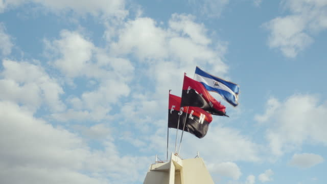 fsln and nicaragua national flag on revolution commemorative monument in leon. two sandinista national liberation front and nicaragua national flags wave on the wind during ruben dario, the poet, anniversary celebration. - nicaragua stock videos and b-roll footage
