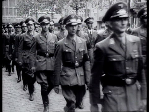 vídeos de stock e filmes b-roll de nsdap and nsb holding joint demonstrative gathering long columns of men dressed in party uniforms proceed through streets / maastricht limburg... - 1942