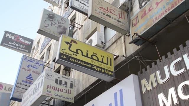 tu and td on shop signs on streets in jordan - シリア難民問題点の映像素材/bロール