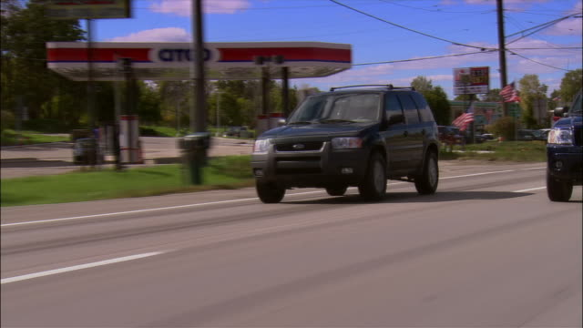 SUV and other cars driving past gas stations on highway near Detroit / Michigan