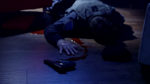 dolly in and out on dead policeman lying on the floor - mord stock-videos und b-roll-filmmaterial