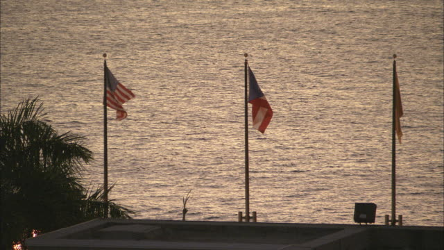 vídeos de stock, filmes e b-roll de ws us and puerto rico flags waving at waterfront at dusk/ san juan, puerto rico - porto riquenho