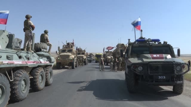 and russian military patrols are seen parked on a road near the northeastern syria border town of al-malikiyah as civilians from the area protest the... - ryssland bildbanksvideor och videomaterial från bakom kulisserna
