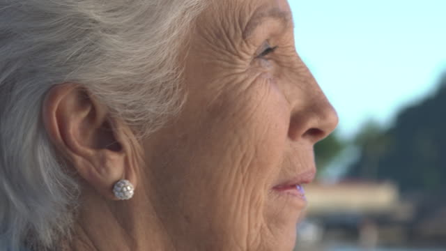 cu and side shot view of a senior lady smiling and turning her face to the camera in a natural daylight with out focus  blue sky, green mountain and sea on the background. - wisdom stock videos & royalty-free footage