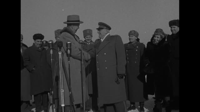 us and soviet union flags flying on double flagpole / at moscow airport us secretary of state george marshall shakes hands with russian deputy... - 冷戦点の映像素材/bロール