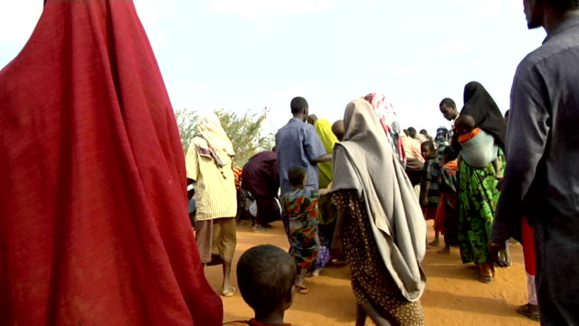and then sitting down at his request at refugee camp People following UN officer with loudspeaker on July 30 2011 in Dadaab Kenya