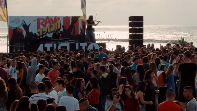dj and violin player on the stage of a rave party on a public square in tel aviv at the sea site. - イスラエル点の映像素材/bロール