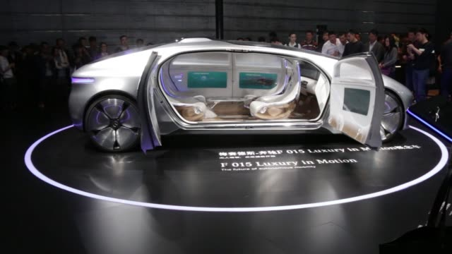MS and WS visitors look at a slow spinning display of a Daimler AG MercedesBenz F015 Luxury in Motion concept vehicle CS logo on badge of a Daimler...