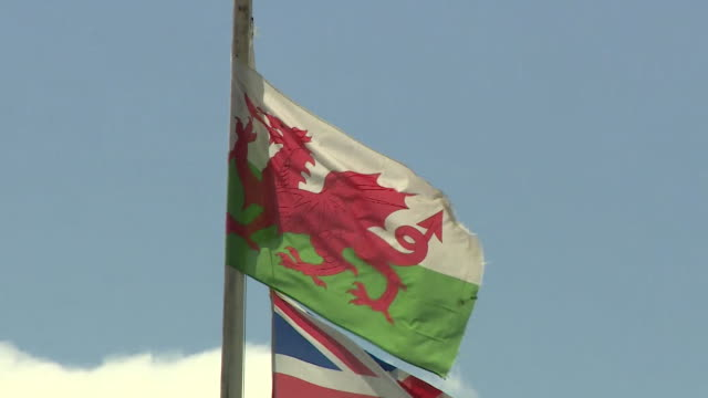 uk and welsh flag blowing in breeze as wales announces travel ban into wales on people visiting from parts of the uk with high coronavirus rates of... - national flag stock videos & royalty-free footage