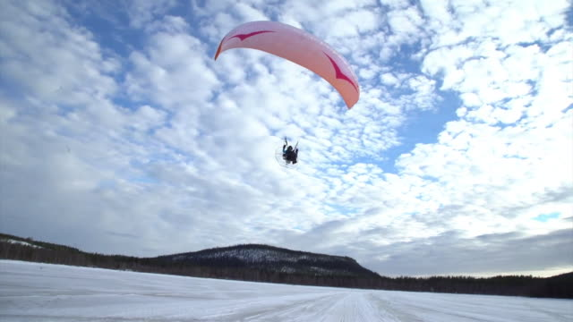 POV and wide shots of a pilot taking off and flying a paramotor