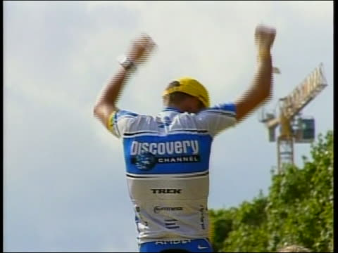 out and zoomin world renown cyclist lance armstrong wins the tour de france and steps onto the winner's platform he puts his hands up in celebration... - sport stock-videos und b-roll-filmmaterial