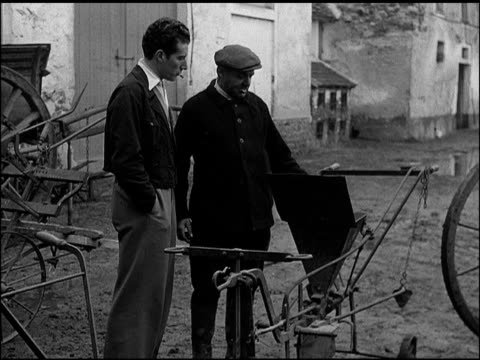 FRANCE DRAMATIZATION 'Andre DuBois' walking w/ 'Cousin Amiel' by barn Amiel showing planting rig 'Cousin Amiel's wife' wrapping food 'Suzanne DuBois'...