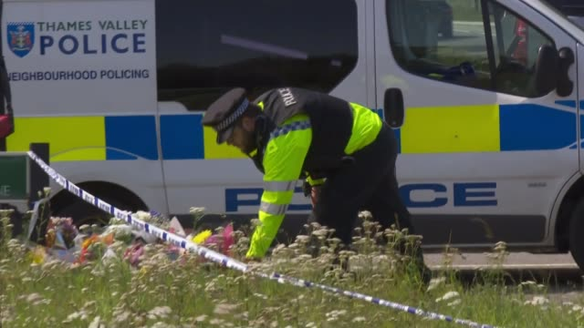 Police given more time to question ten suspects ENGLAND Berkshire Sulhamstead EXT Police officer laying floral tribute Floral tributes for PC Andrew...