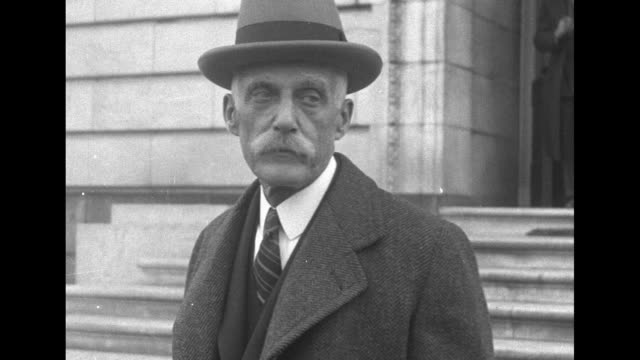 Andrew Mellon Pres Herbert Hoover's new Secretary of the Treasury stands outdoors wearing overcoat and fedora / Note exact month/day not known