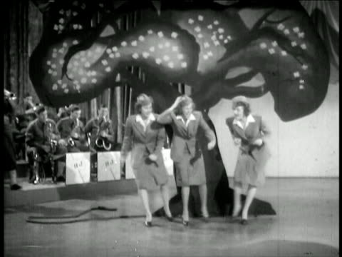 vidéos et rushes de andrews sisters in uniform singing together / collide + fall down / feature film - 1942